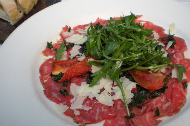 Wagyu Carpaccio with wild rocket, semi-dried tomato, truffle oil and crisp parsley